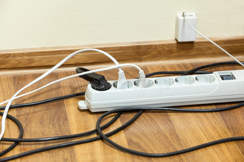 Beaucoup de cordes électriques reliées au bloc d'extension image stock