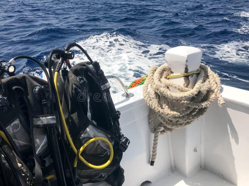 Beaucoup de costume de plongée noir avec des tuyaux et vestes de plongée accrochent sur le support et une corde lourde sur un bat photo stock