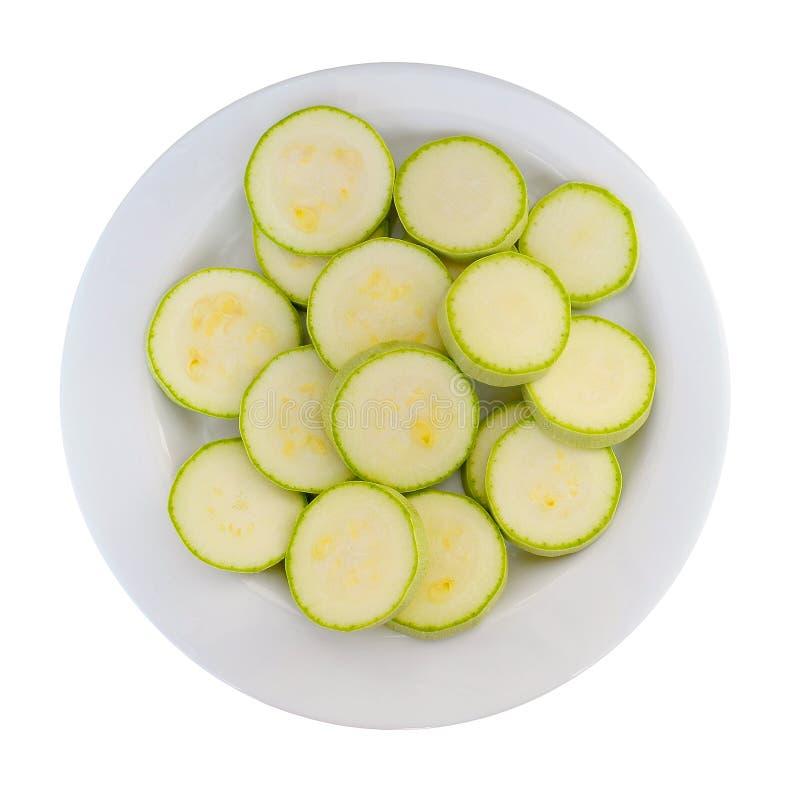 Beaucoup de courgette crue fraîche a coupé en anneaux d'un plat blanc, vue supérieure, d'isolement sur le blanc image stock