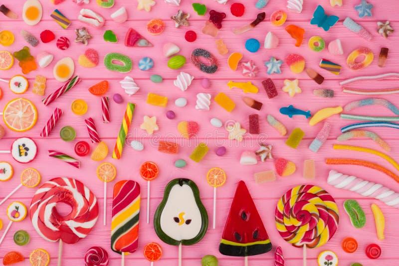 Beaucoup de différentes sucreries sur le fond en bois rose photographie stock