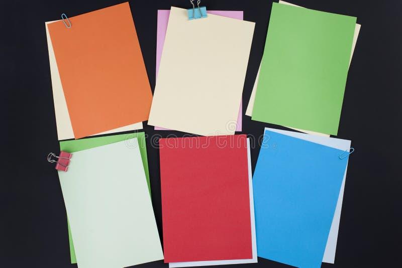 Beaucoup de différents papiers colorés pour des notes sur un fond noir Concept de bureau Copiez l'espace images stock