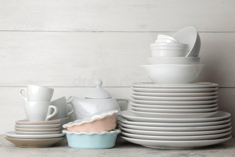 Beaucoup de différents plats vaisselle sur un fond de ciment plats pour servir la table divers plats, cuvettes, et Cu photos stock