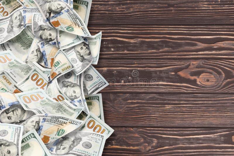Beaucoup de dollars sur un fond en bois image stock
