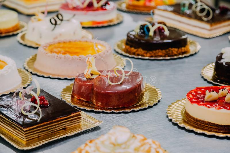 Beaucoup de gâteaux préparés sur la table en métal d'une usine de nourriture image stock