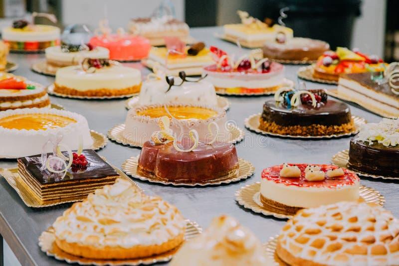 Beaucoup de gâteaux préparés sur la table en métal d'une usine de nourriture photos libres de droits