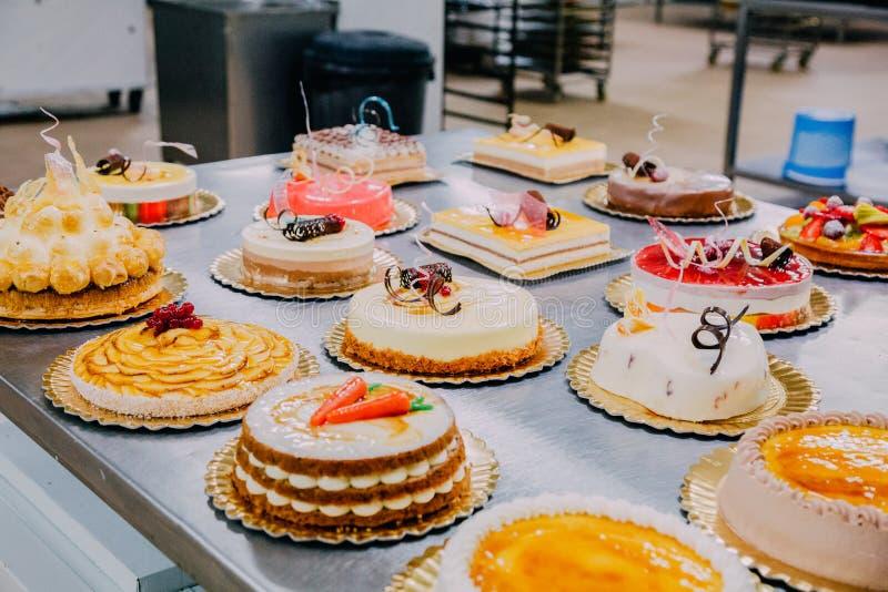 Beaucoup de gâteaux préparés sur la table en métal d'une usine de nourriture photographie stock libre de droits