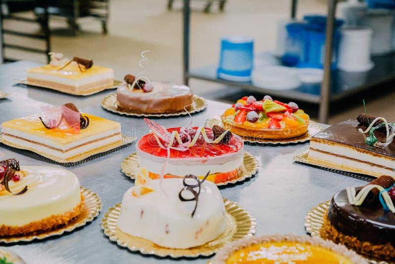 Beaucoup de gâteaux préparés sur la table en métal d'une usine de nourriture image libre de droits