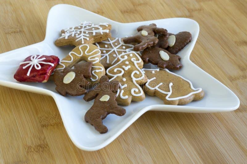Beaucoup de genres de biscuits de Noël du plat blanc, pain d'épice foncé et léger, plat de forme d'étoile, fond en bois en bambou photos libres de droits