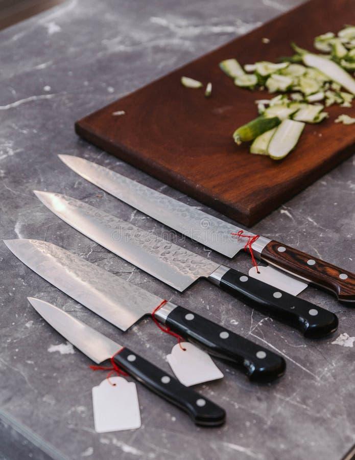 Beaucoup de genres de couteaux de cuisine japonais pointus superbes avec la courgette de tranche ultra mince sur le hachoir en bo images libres de droits
