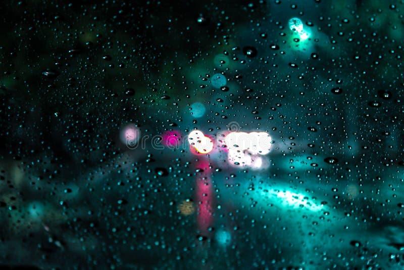 Beaucoup de gouttelettes sur une fenêtre de voiture dans le feu vert bleu photo stock