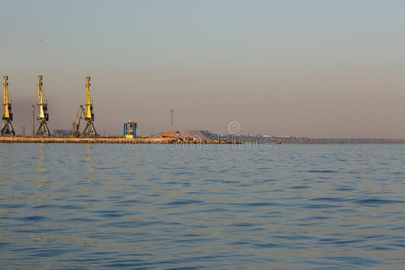 Beaucoup de grandes grues silhouettent dans le port maritime d'Azov ? la lumi?re d'or du coucher du soleil mariupol photo libre de droits