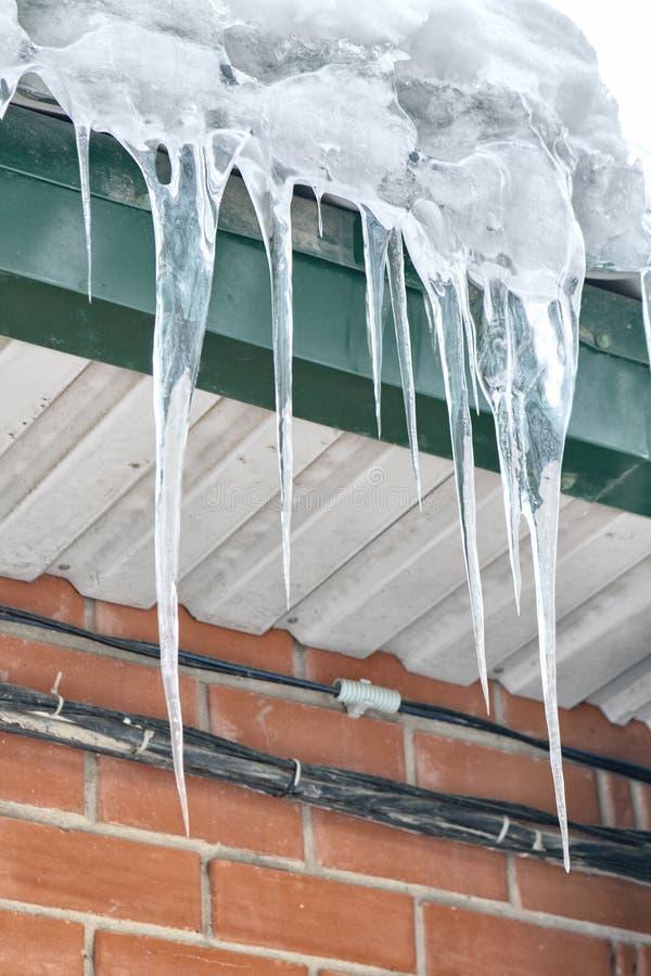 Beaucoup de grands glaçons sur le toit d'hiver un jour ensoleillé image stock