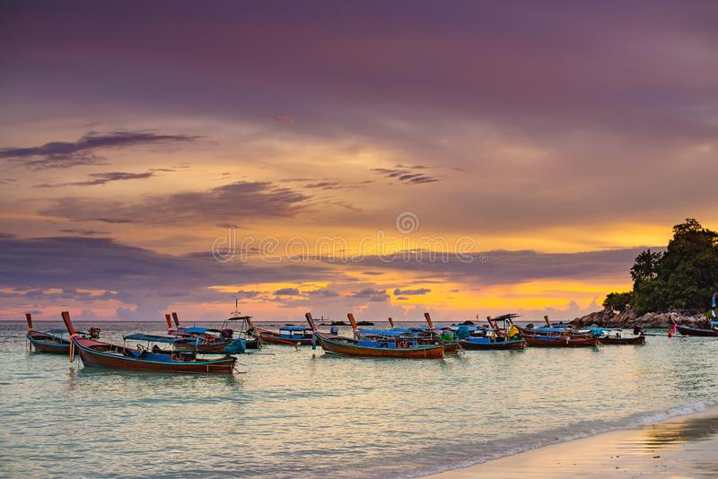 Beaucoup de longs bateaux flottent en mer avec la belle vue étonnante de coucher du soleil d'été à la plage Thaïlande de Lipe photographie stock