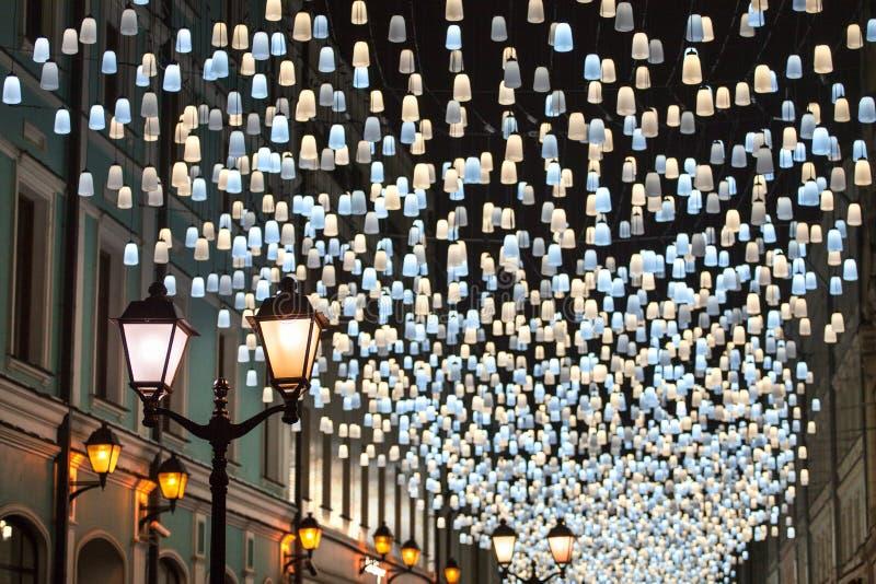 Beaucoup de lumières brûlantes lumineuses bleues et lanternes jaunes accrochant sur le plan rapproché noir de fond de ciel noctur photo libre de droits