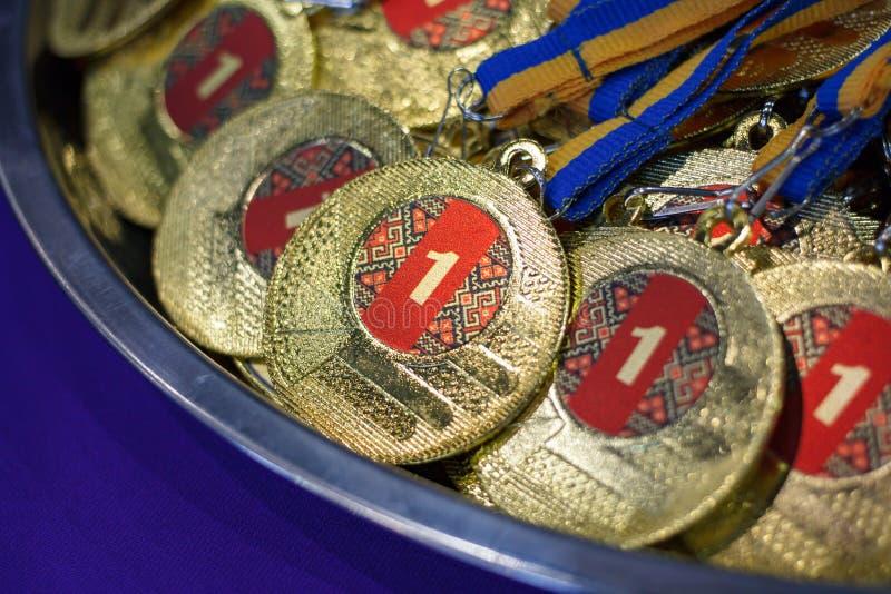 Beaucoup de médailles d'or avec les rubans jaunes sur un plateau argenté, récompenses des champions, accomplissements de sport, p image libre de droits