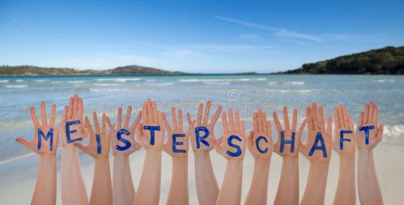 Beaucoup de mains construisant Meisterschaft signifie le championnat, la plage et l'océan photos libres de droits