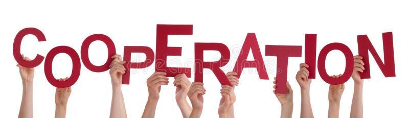 Beaucoup de mains de personnes tenant la coopération rouge de Word image libre de droits