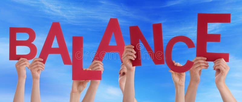 Beaucoup de mains de personnes tiennent le ciel bleu d'équilibre rouge de Word images libres de droits