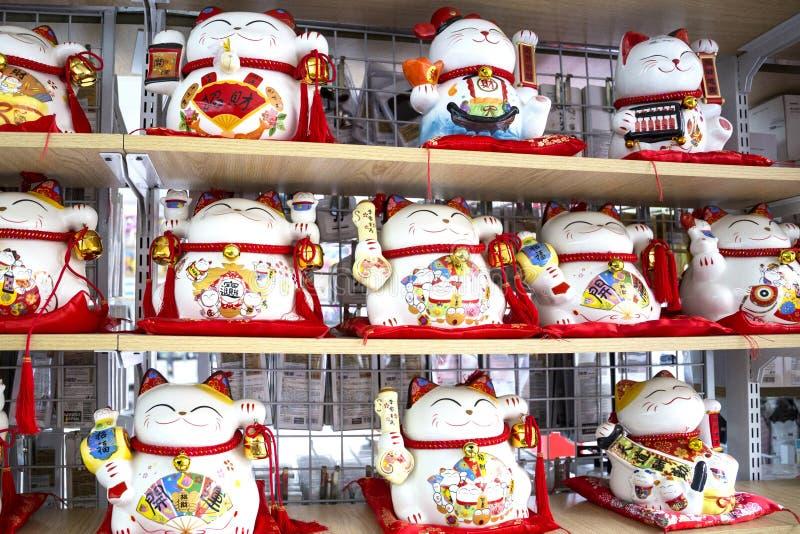 Beaucoup de mascotte traditionnelle mignonne de jouet montrant le chat du doigt images stock