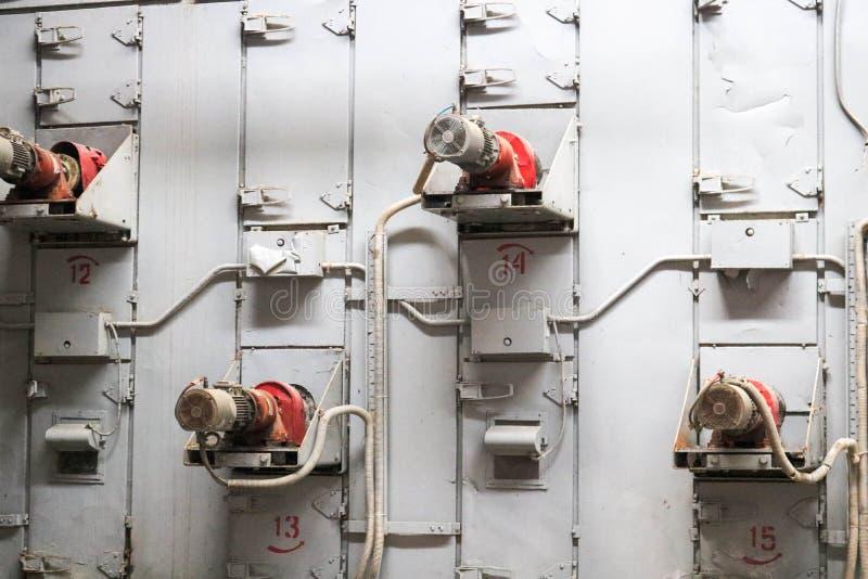 Beaucoup de moteurs électriques asynchrones en métal industriel dans le mur gris de fer à un renforcement de machine, chimique, p photos libres de droits