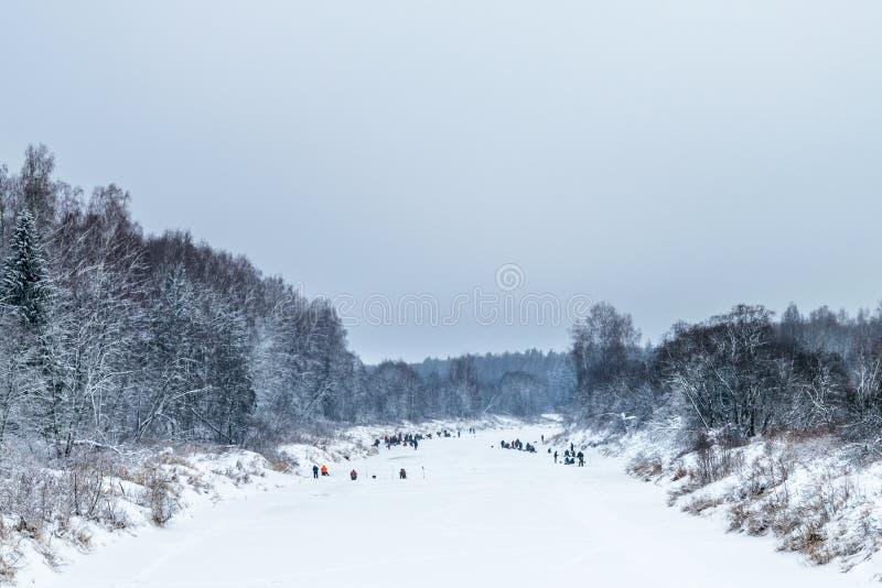 beaucoup de pêcheurs pour attraper la pêche d'hiver de poissons sur la rivière images stock