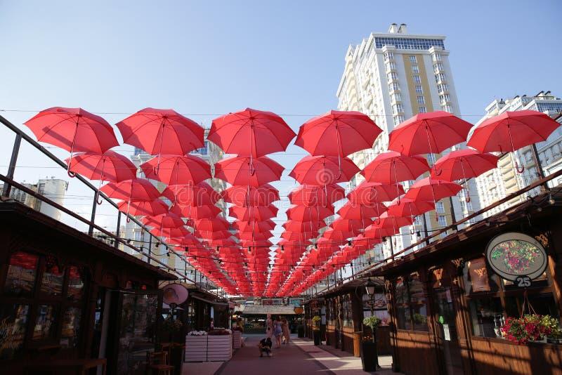 Beaucoup de parapluies de corail rouges contre le ciel bleu et le bâtiment lumineux Fond abstrait avec des parapluies photo libre de droits