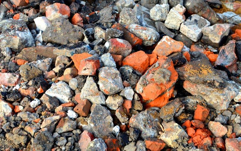 Beaucoup de pavés ronds de granit sur la terre ou la route cassée, fragments des briques, peuvent être utilisés image libre de droits