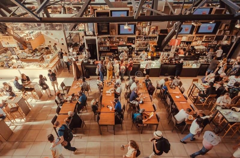 Beaucoup de personnes buvant et mangeant à l'intérieur de l'espace restauration rapide du marché central, avec les magasins exoti image stock