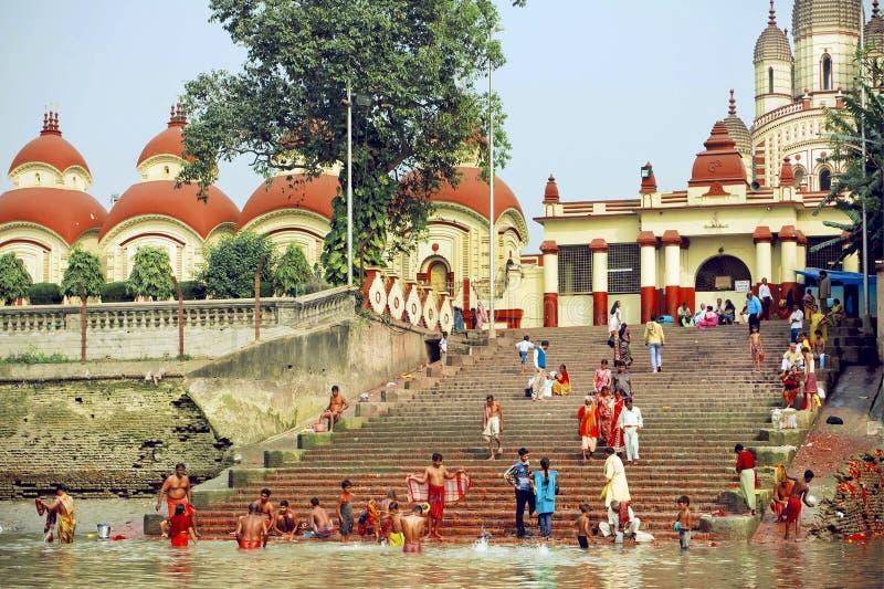 Beaucoup de personnes se baignant dans l'eau du temple historique de Kali de passé de rivière photographie stock libre de droits
