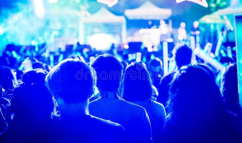 Beaucoup de personnes sont dans le concert local et tous elles se tenant devant l'étape photographie stock