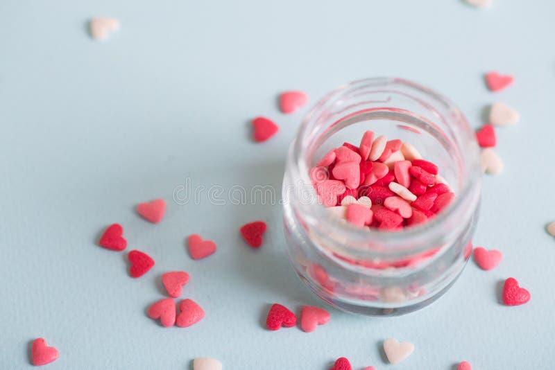 Beaucoup de petite sucrerie sous la forme de coeurs dans le pot en verre ouvert sur le fond clair photo libre de droits