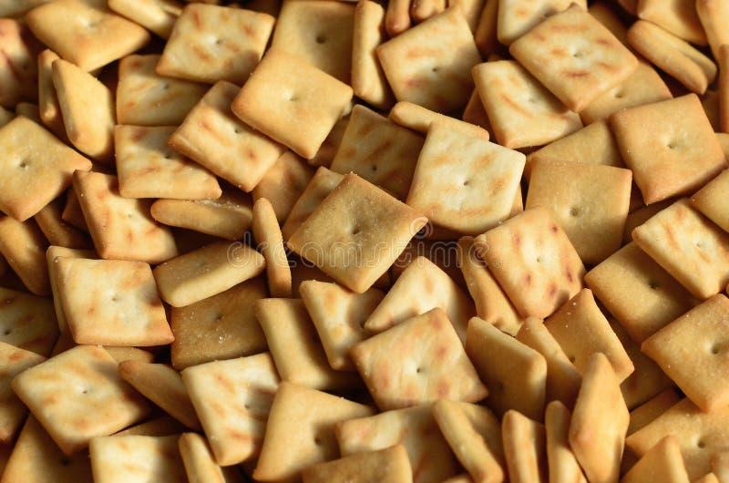 Beaucoup de petits biscuits sont à angle droit formé Un modèle d'un biscuit jaune de sel Fond d'image avec le pastr salé photo libre de droits