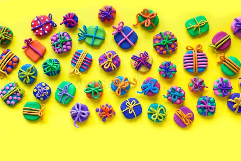 Beaucoup de petits cadeaux de pâte à modeler Fond jaune images stock