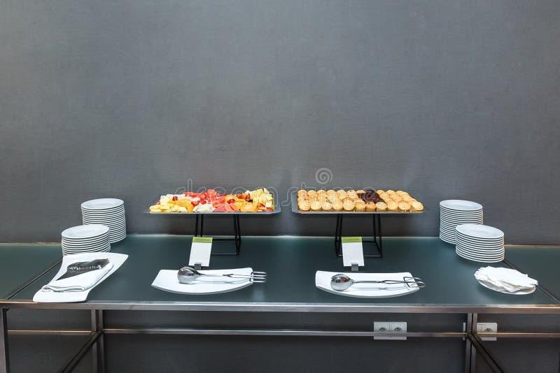 Beaucoup de petits pains doux et de fruits coupés en tranches sur la table sur une pause-café dans le bureau photo libre de droits