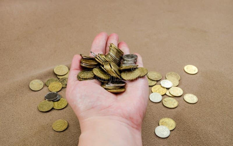Beaucoup de pièces de monnaie dans la main femelle image stock