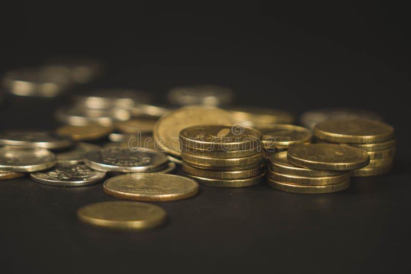 Beaucoup de pièces de monnaie ont dispersé d'une façon chaotique sur un fond noir photographie stock libre de droits