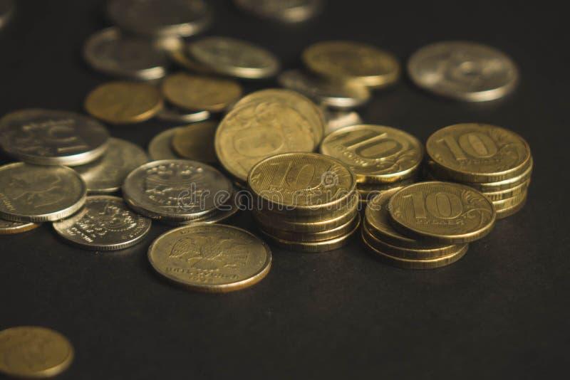 Beaucoup de pièces de monnaie ont dispersé d'une façon chaotique sur un fond noir image stock