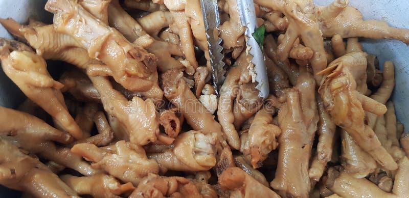 Beaucoup de pied ou de jambe bouilli ou cuit à la vapeur de poulet avec les pinces inoxydables dans la cuvette d'acier inoxydable image libre de droits