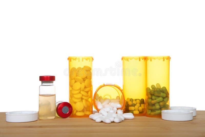 Beaucoup de pilules et de fioles de bouteilles de médicament sur une table en bois image libre de droits