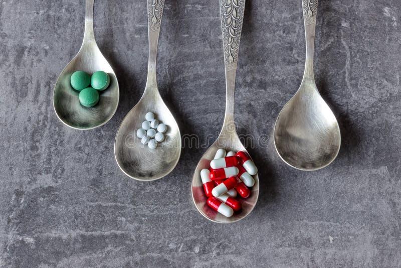 Beaucoup de pilules et médecines colorées, vitamines, capsules dans une cuillère sur un fond foncé photos libres de droits