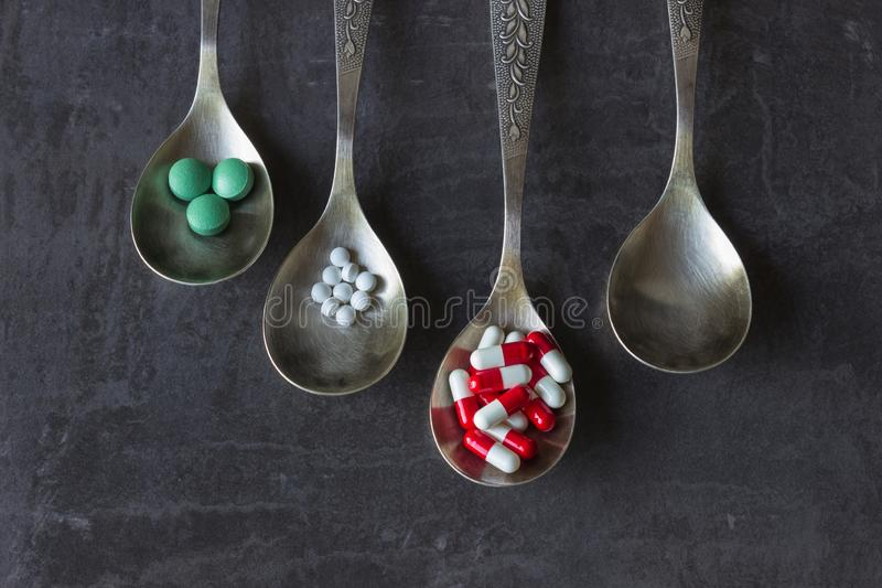 Beaucoup de pilules et médecines colorées, vitamines, capsules dans une cuillère sur un fond foncé image stock