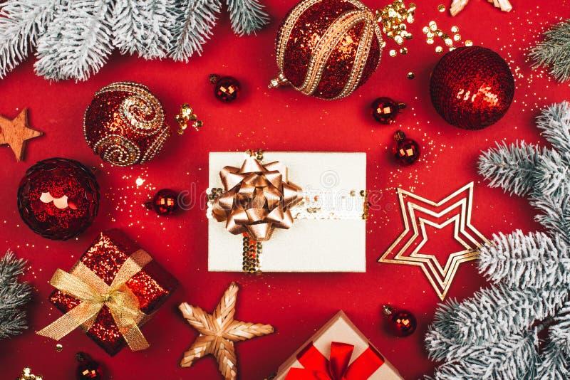 Beaucoup de présents parmi les décorations de scintillement de Noël sur le fond rouge photos libres de droits