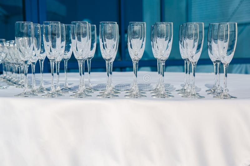 Beaucoup de rangées des verres à vin vides à la table blanche Verre de bienvenue restauration images libres de droits