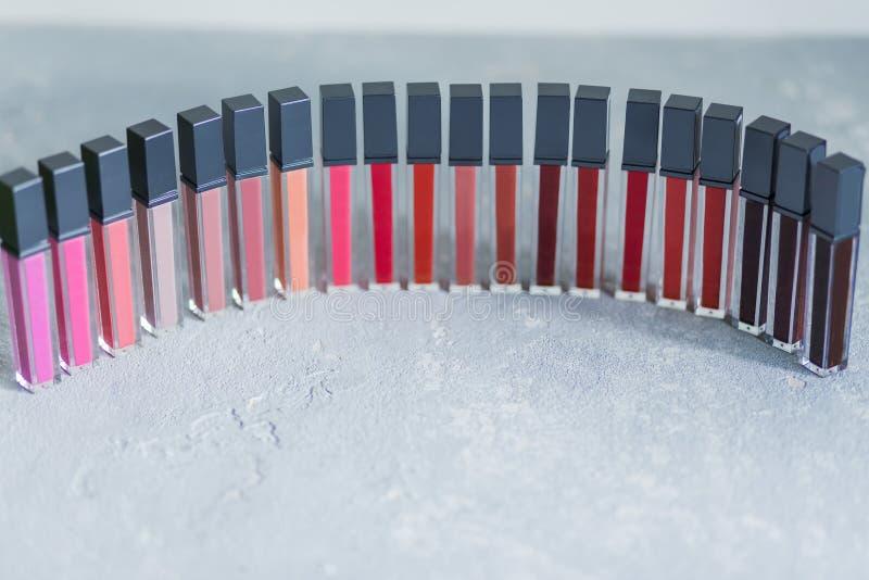 Beaucoup de rouge à lèvres professionnel coloré et lumineux a aligné dans les rangées, sur le fond gris blanc, plan rapproché, ma photo stock
