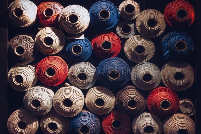 Beaucoup de rouleaux de textile de couleurs bleues, blanches et oranges ont empilé un au-dessus de l'autre images stock