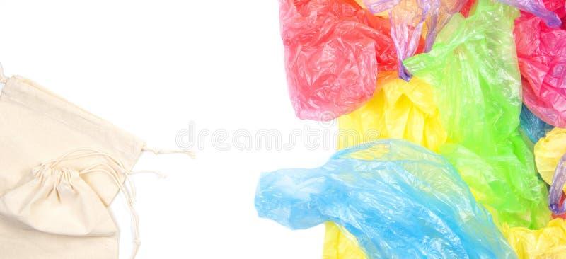 Beaucoup de sachets en plastique à usage unique avec deux sacs à provisions réutilisables naturels d'eco sur le fond blanc D?chet photographie stock
