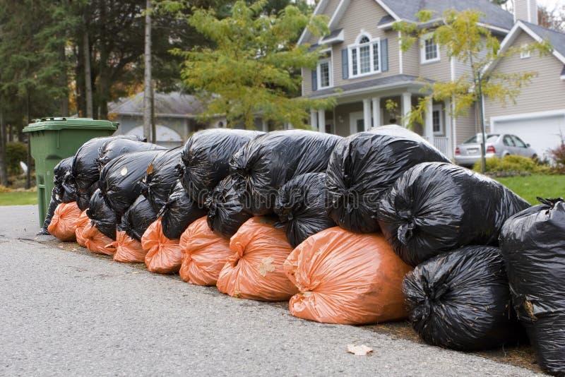 Beaucoup de sacs d'ordures oranges et verts à la bordure de trottoir photo stock