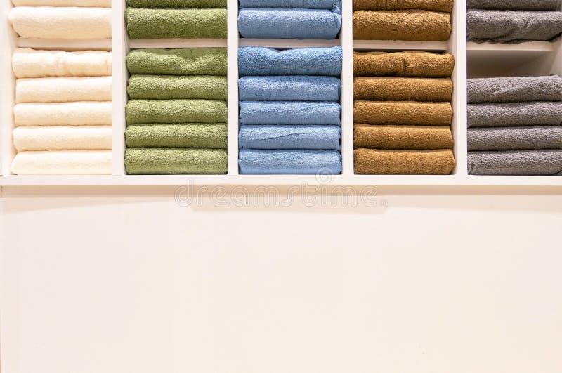 Beaucoup de serviettes colorées se plie dans les shelfs au magasin à vendre illustration stock