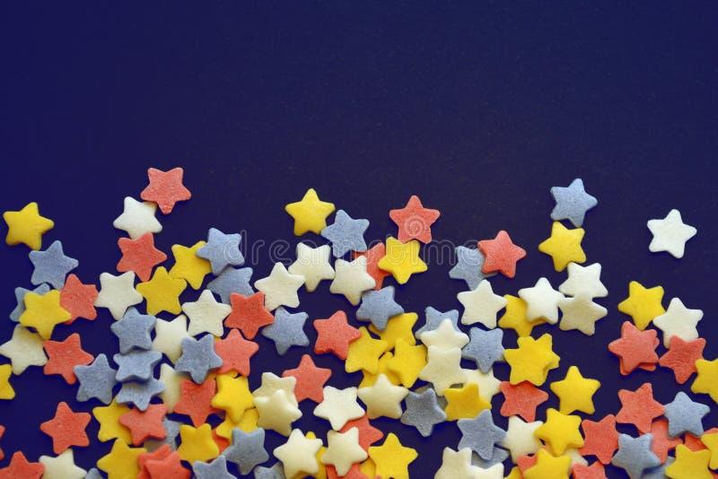 Beaucoup de sucre a coloré des étoiles sur le fond du macro bleu de fond, fond pour des confiseurs avec le copyspace photos libres de droits