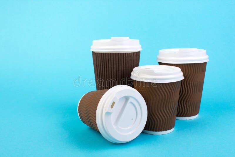 Beaucoup de tasses de café de papier jetables, thé sur le fond bleu photographie stock libre de droits